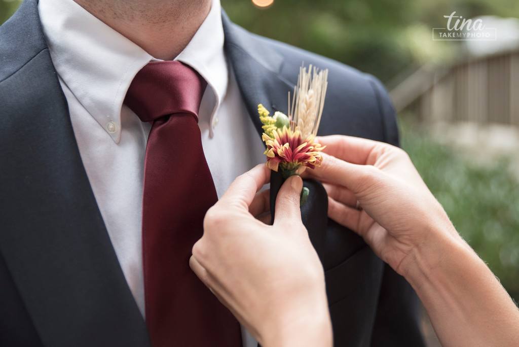 pinning-boutineer-flower-lapel-navy-maroon-preppy-tie-suit-Richmond-virginia-wedding-photographer-tina-take-my-photo-fall-celebrations-reservoir-midlothian